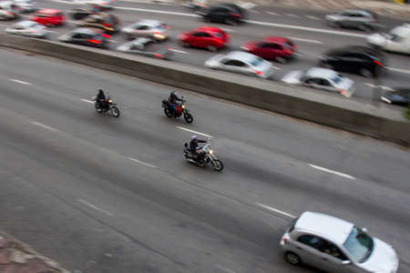 Pan shoot of motorcycles at high speed on an avenue in downtown from a nearby building with slower cars opposite direction lane. No people.
