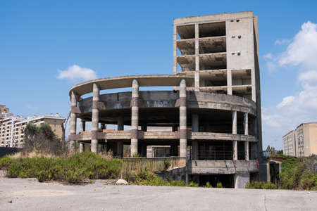Huge multi floors concrete structure of abandoned building with stairs surrounded by grass and trees with blue sky in the background. Architecture detail. No people. Banque d'images