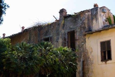 Old abandoned building with trees on the outside near a yellow painted house. Banque d'images