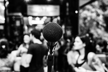 Black and white wallpaper background of a microphone in the street in front of a bar full of people on a happy hour after work on a summer afternoon in the metropolis.
