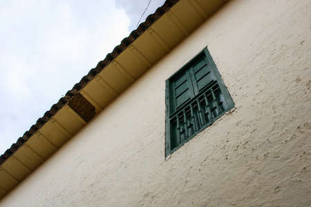 Low angle view of a white rough wall with green wood window and orange shingles roof of a house in Cusco, Peru, with blue sky with clouds on the background.