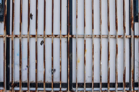 Closed white bars rusty metallic gate detail. Banque d'images