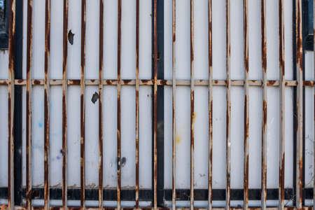 Closed white bars rusty metallic gate detail. 写真素材