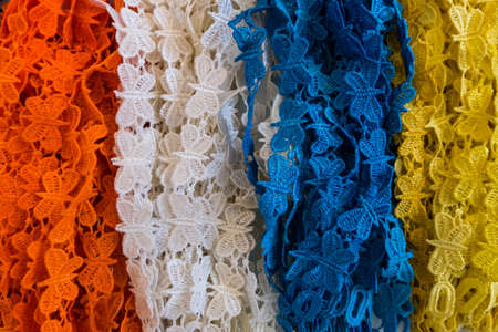 Wallpaper background of colorful options of fabric laces in orange, white, blue and yellow at a fashion store.