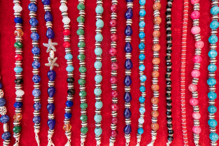 Wallpaper background of a flea market stall with fake vintage jewelery bracelets and necklaces for sale.