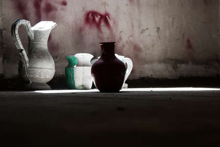 Wallpaper background of old vintage worn green ceramic water vases on the floor near a window with day light from the outside. No people. 写真素材