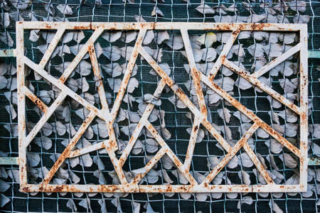 Wallpaper background of rusty white geometric structure on a green fabric wall. 写真素材
