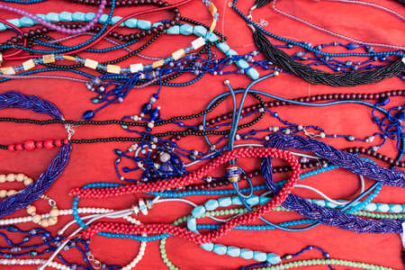 Wallpaper background of colorful bracelets and necklaces for sale at a flea market with red velvet background. Banque d'images