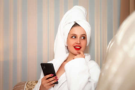 Girl of Slavic appearance with phone and white Cup is sitting at table. Female takes actor's emotions. Young charming woman is sitting in hotel room and drinking coffee or tea with smartphone