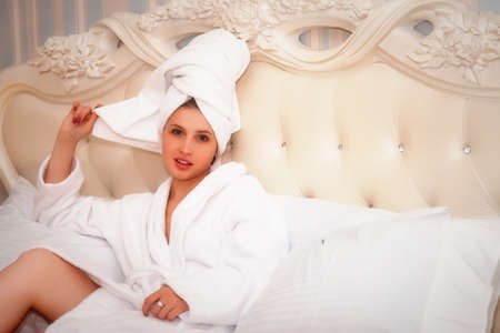 Girl of Slavic appearance in white coat on bed in hotel room. Pretty female shows acting emotions. Young charming woman is sitting on sofa in bedroom and playing with her feelings. Relax concept