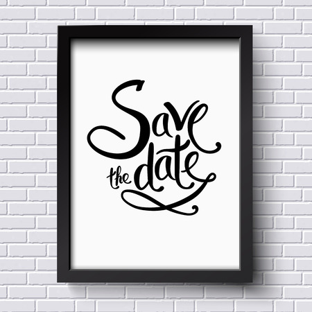 Simple Text Design for Save the Date Concept on a Black and White Frame Hanging on a White Brick Wall.