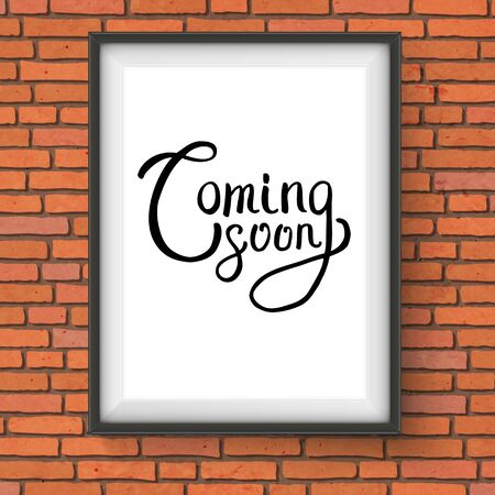 scrip: Conceptual Coming Soon Phrase in Black Font Style Inside a White Frame Hanging on a Brick Wall.
