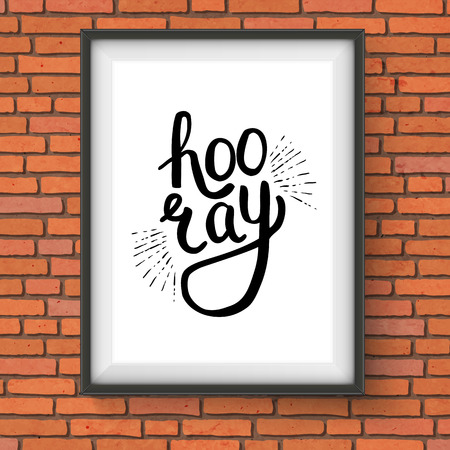 overjoyed: Close up Conceptual Hooray Text in a Stylish Black Font Style Inside a White Frame Hanging on Brick Wall