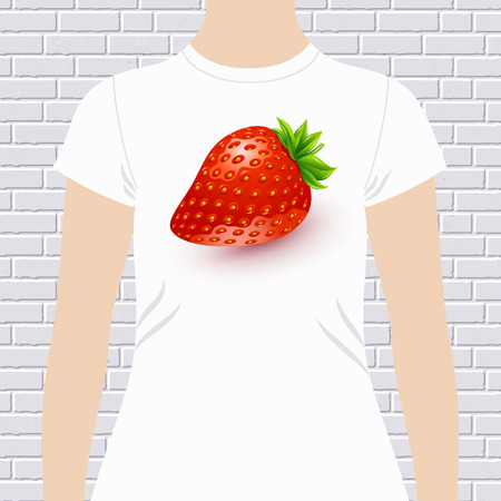 tempting: Fun t-shirt design template with a luscious ripe red fresh ripe strawberry on a white garment modeled by a woman over a white brick wall