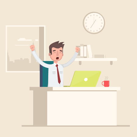 A man sits in the workplace in the office and yawns.
