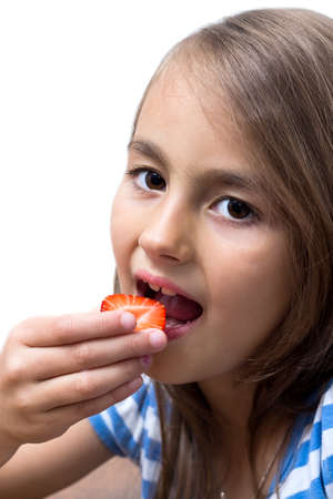 Happy little girl eats strawberries, isolated over white photo