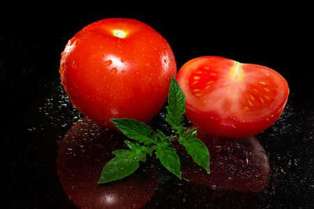 Red tomato on black background  photo