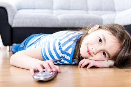 cute little girl holding a remote control photo