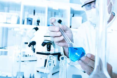 laboratorio clinico: cient�fico que trabaja en el laboratorio, en la m�scara protectora y la tapa, examina un tubo de ensayo con el l�quido