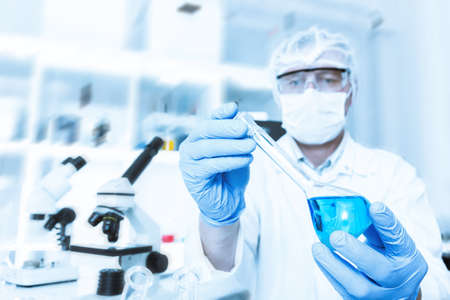 scientist working in the lab, in protective mask , examines a with liquid