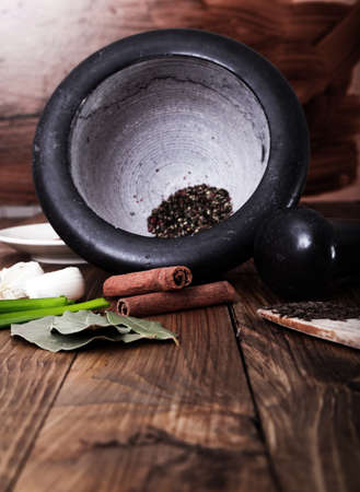 Tree spoons with spices and a bundle of herbs, mortar and pestle