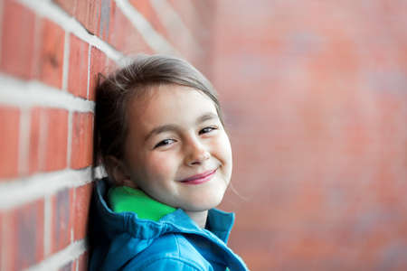 Portrait of  happy little cute girl next to Brick Wall