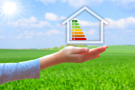 clean energy: hands holding house with energy efficiency rating
