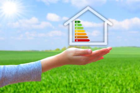 manos que sostienen la casa con clasificación de eficiencia energética Foto de archivo