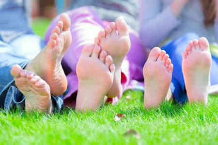 Group of happy children lying on green grass in park photo
