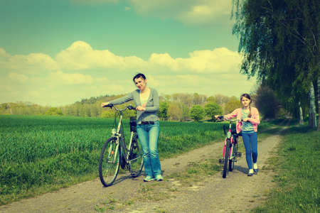 Young girl with mother on bikes  in the countryside,with a retro vintage photo