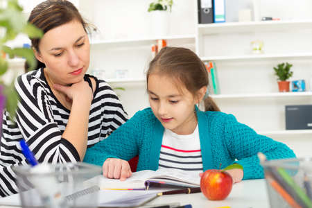 listless: Mother Helping Daughter With Homework Stock Photo