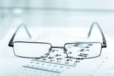 sight chart: Modernas gafas negras claras sobre una carta de prueba de la vista del ojo.