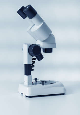 microscope lens: Scientific microscope lens on blue , A microscope is an instrument used to see too small objects