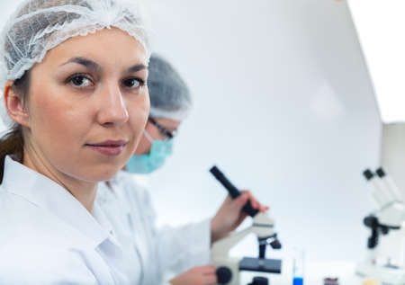 scientist woman: Team of scientists in a laboratory working on chemical testing.