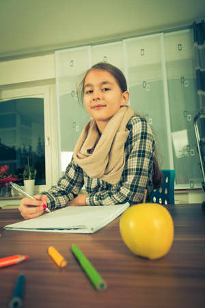 working on school project: Beautiful  girl working on her school project at home.