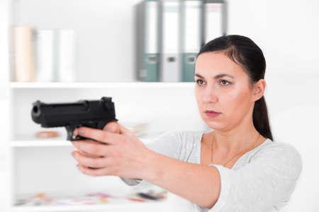 Beautiful woman aiming gun.