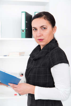 overloading: Business woman in the office embracing a pile of folders.