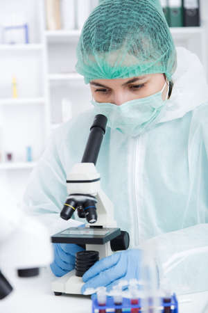 Woman working with a microscope in a lab.Toning image