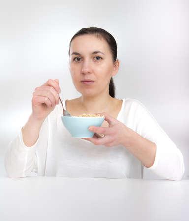 comiendo cereal: Retrato de mujer joven en ropa interior comer los cereales. en blanco. Mujer joven que come la muselina del cereal (escamas)
