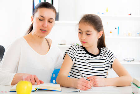 listless: Mother Helping Daughter With Homework. Stock Photo