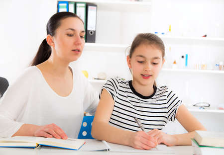 the weariness: Mother Helping Daughter With Homework. Stock Photo