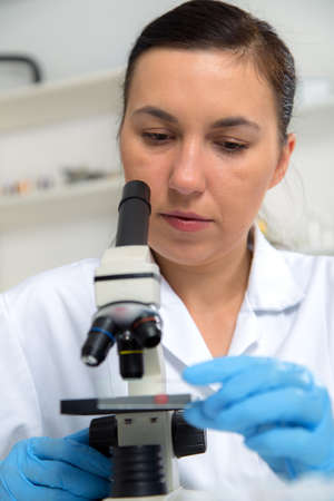 laboratorian: Woman working with a microscope in a lab.Toning image. Stock Photo