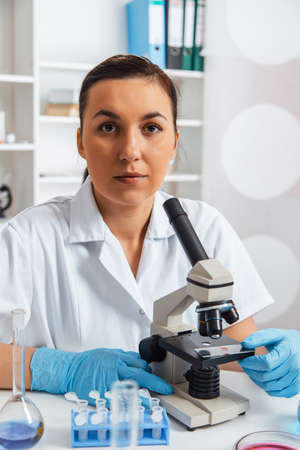 laboratorian: Woman working with a microscope in a lab.Toning image
