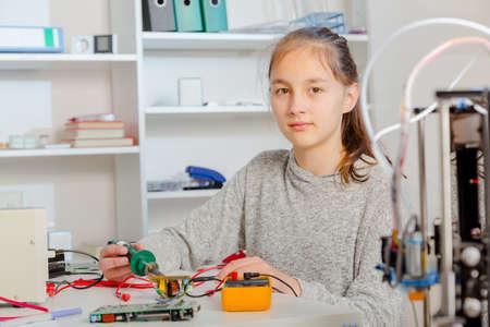 Schoolgirl  repairing the electronic printed circuit board.Computer repair
