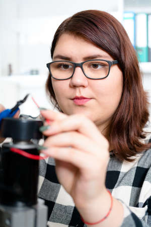 Teenage girl working on CNC machinery.
