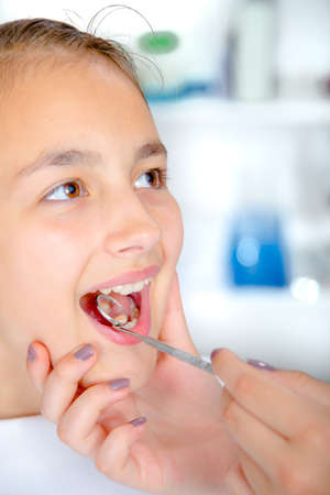 Close-up of little girl opening his mouth wide during treating...