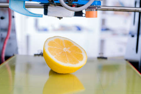 Ripe slice of yellow lemon citrus fruit . 3d printer of the device during the processe