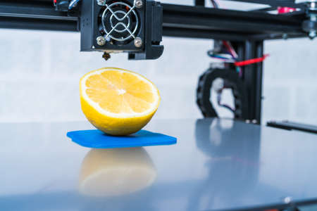 Ripe slice of yellow lemon citrus fruit . 3d printer of the device during the processe. Banco de Imagens