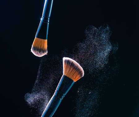 Make up brush with  powder explosion on black background.