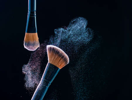 Make up brush with  powder explosion on black background.
